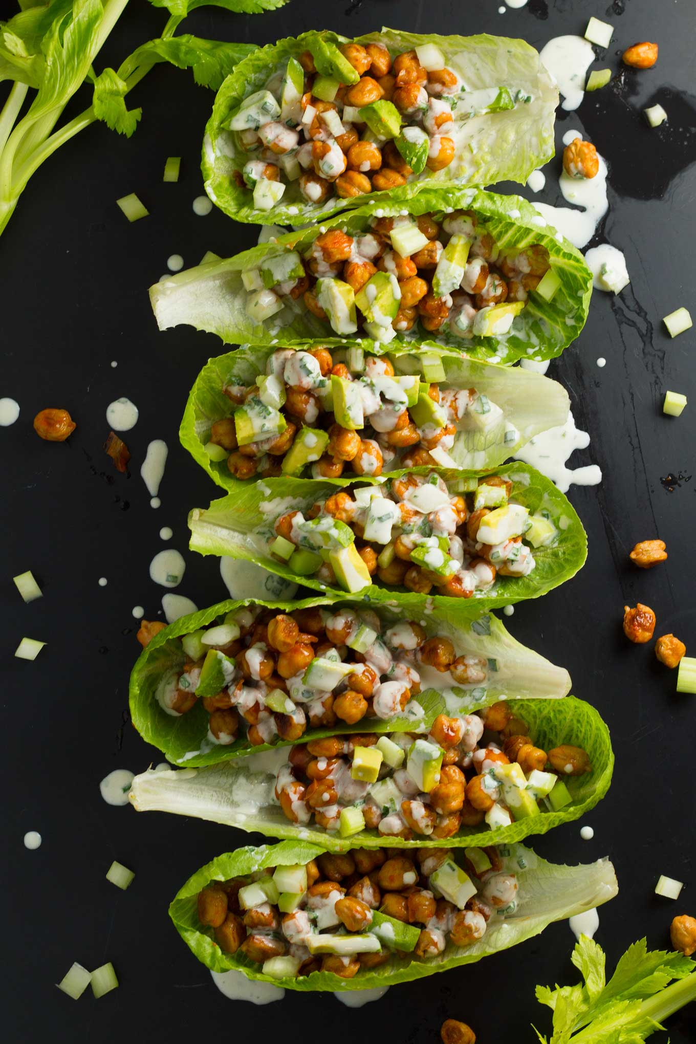 Buffalo Chickpea Lettuce Wraps | Roasted chickpeas are tossed with a spicy buffalo sauce and layered into a lettuce wrap, then topped with crunch celery and creamy avocado! Drizzle with vegan ranch dressing for the perfect lunch or light dinner! | http://eatwithinyourmeans.com