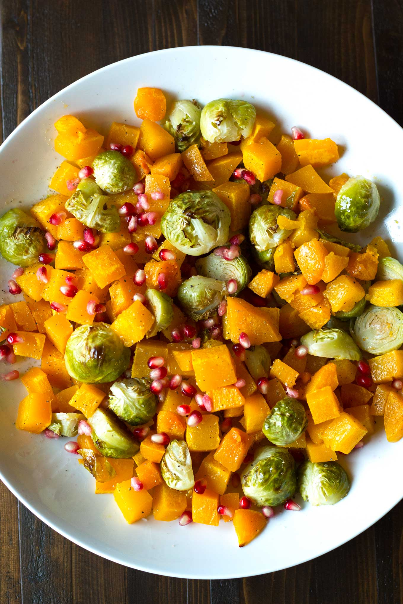 Fall Roasted Vegetables | Roasted butternut squash, brussels sprouts, sprinkled with pomegranate arils | Easy Vegan Side Dish | https://eatwithinyourmeans.com