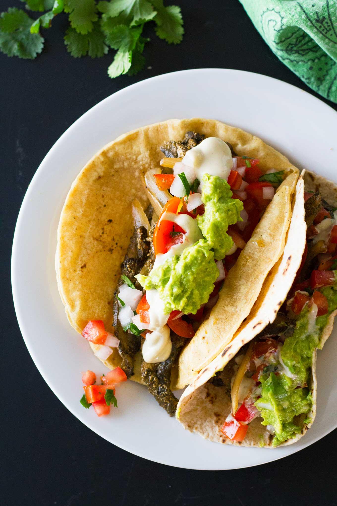 Ultimate Vegan Fajitas | Assembled fajitas on a plate topped with guacamole, pico de gallo, savory cashew cream | https://eatwithinyourmeans.com/