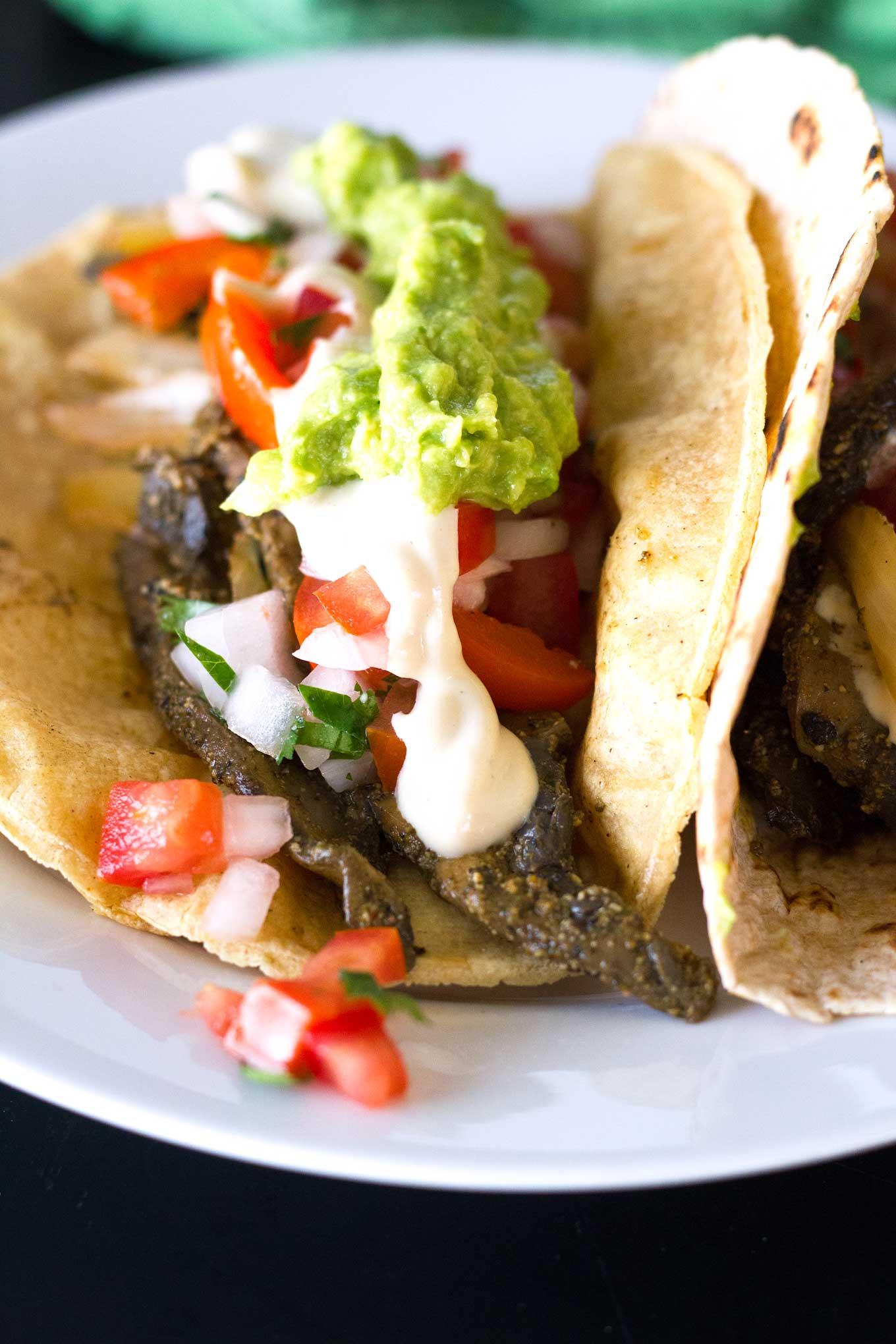 Ultimate Vegan Fajitas | Close-up of assembled fajitas on a plate topped with guacamole, pico de gallo, savory cashew cream | https://eatwithinyourmeans.com/