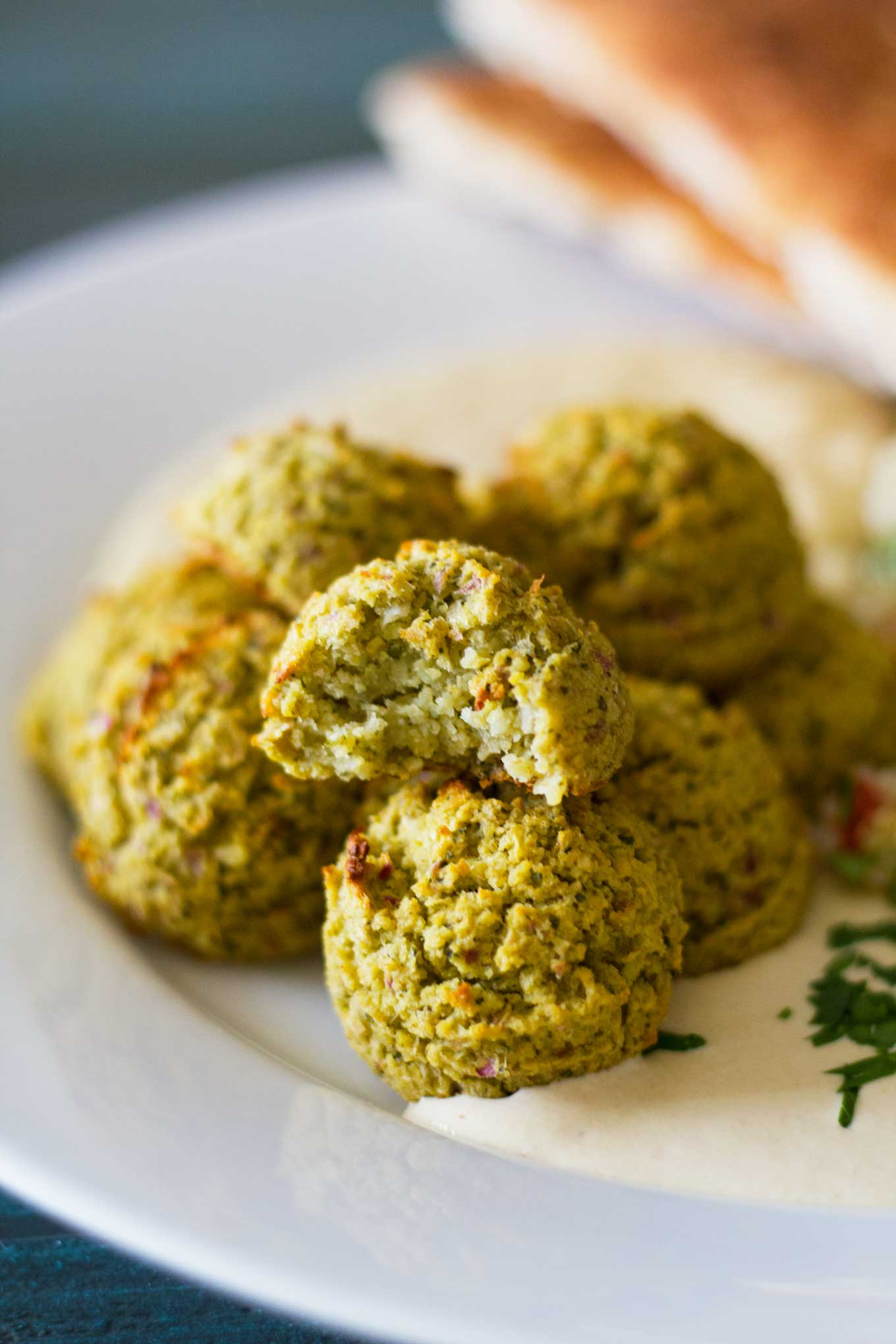 Oven-Baked Falafel close-up with a bite taken out | Plant-based | Oil-free | Vegan | Gluten-free | https://eatwithinyourmeans.com/