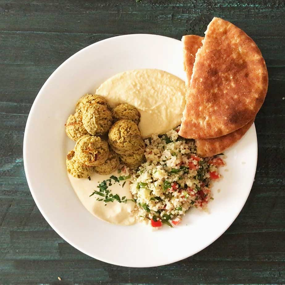 Oven-Baked Falafel in mezze platter with hummus, tahini sauce, quinoa tabouli salad, and pita bread | Plant-based | Oil-free | Vegan | Gluten-free | https://passtheplants.com/