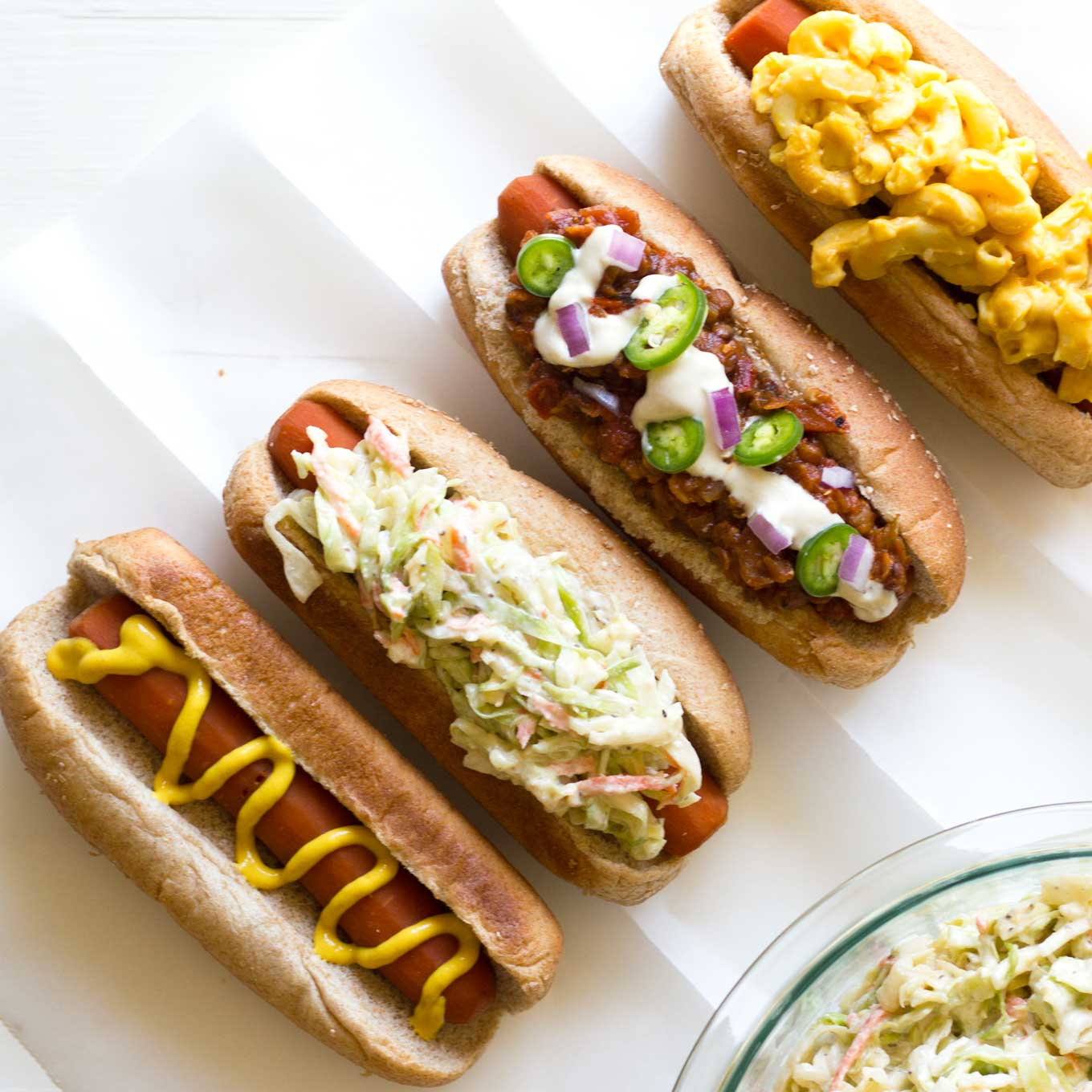 Close up of carrot dogs with various toppings   Easy Carrot Dogs   Plant-based   Vegan   Recipe   https://passtheplants.com/