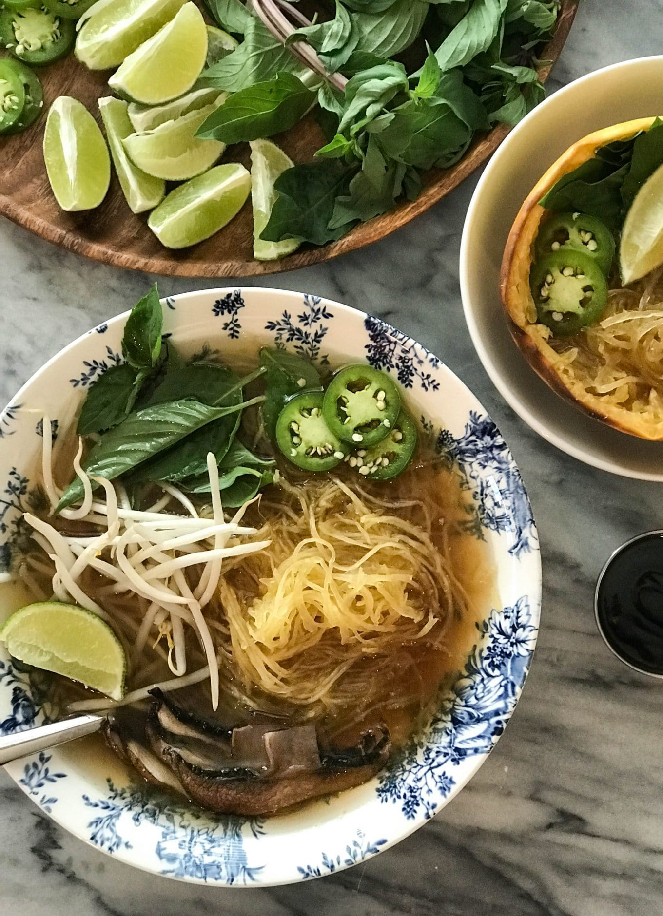 Spaghetti Squash Vegan Pho   Soup in bowl with roasted portobello mushrooms and toppings   https://eatwithinyourmeans.com/