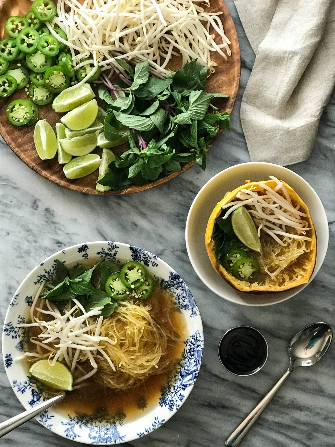 Spaghetti Squash Vegan Pho   Pho in bowls with toppings of mung bean sprouts, lime, jalapeño, thai basil   https://eatwithinyourmeans.com/