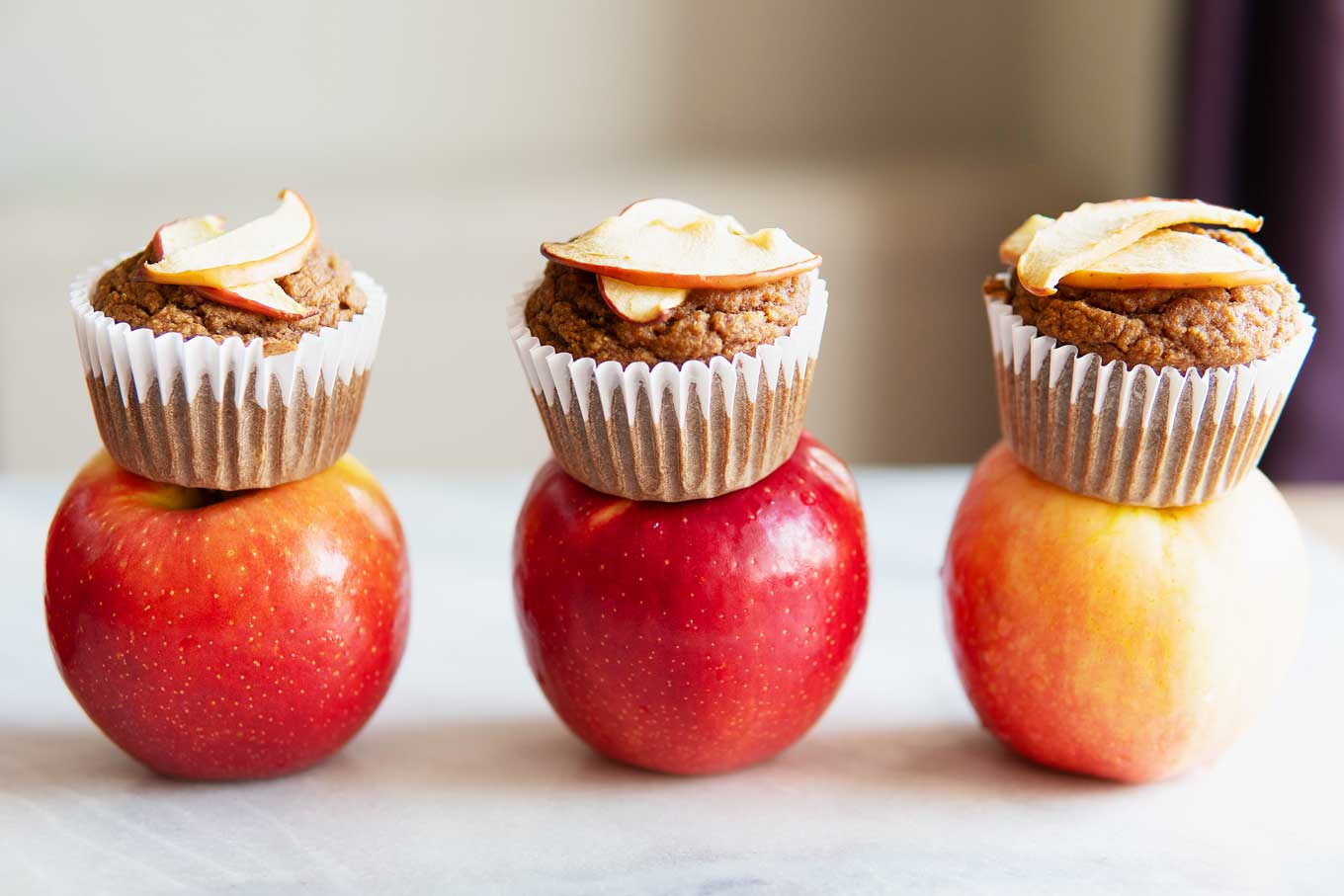 apple cinnamon blender muffins sitting atop three apples