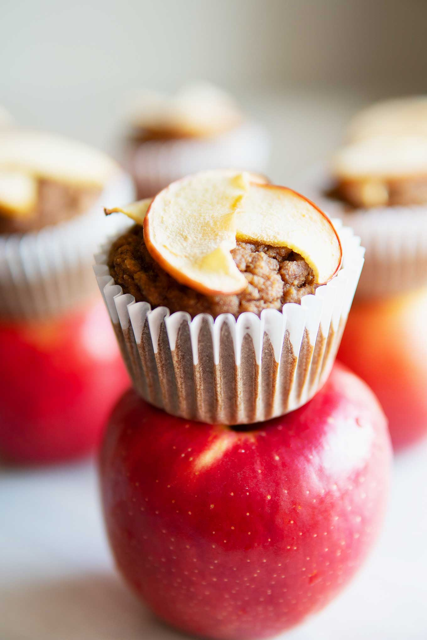 apple cinnamon almond blender muffin sitting on top of a raw apple