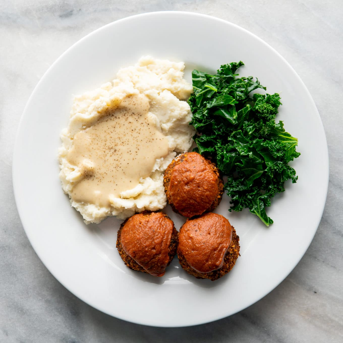 vegan meatloaf cups on a white plate with mashed potatoes and kale